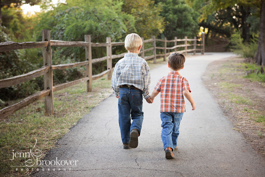 boys holding hands and walking down the path at Denman Estates Park during photo session
