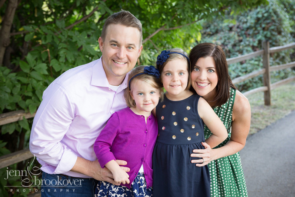 family in purple, blue and green smiling for their family portrait at Denman Estates