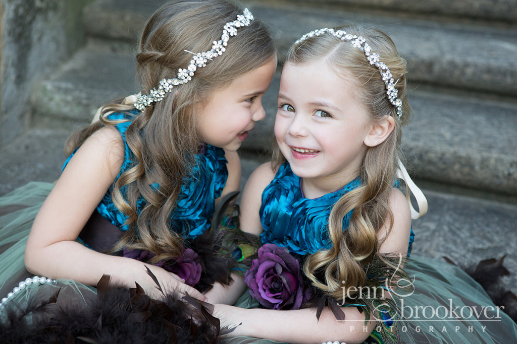 sisters giggling wearing crystal headbands dressed in purple and teal for their family portraits at McNay