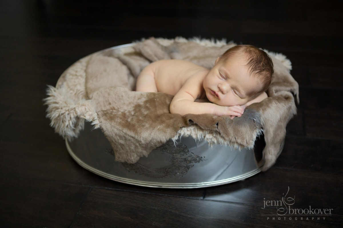 newborn in silver bowl during photo shoot at home, fur