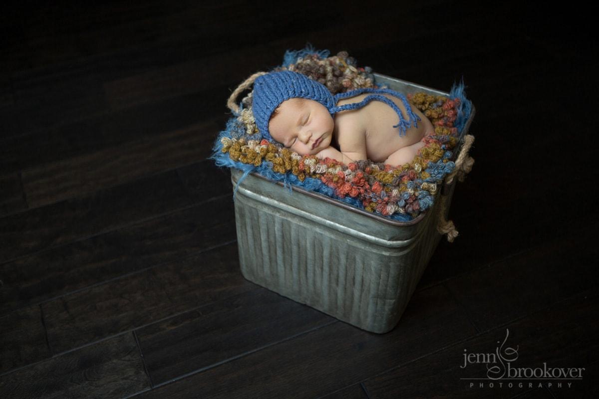 newborn photo on orange, blue and brown blanket wearing blue knitted hat, wood floor