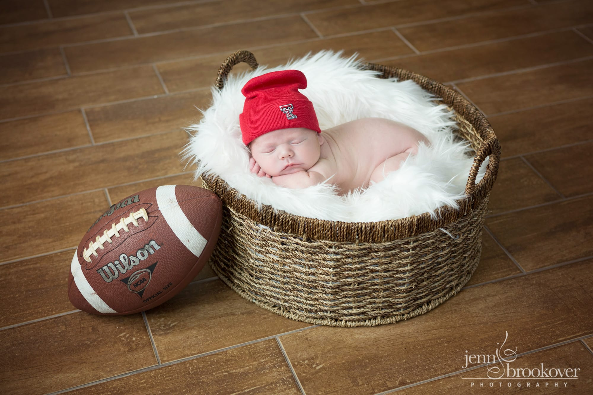 newborn boy in Texas Tech gear with football during photo session