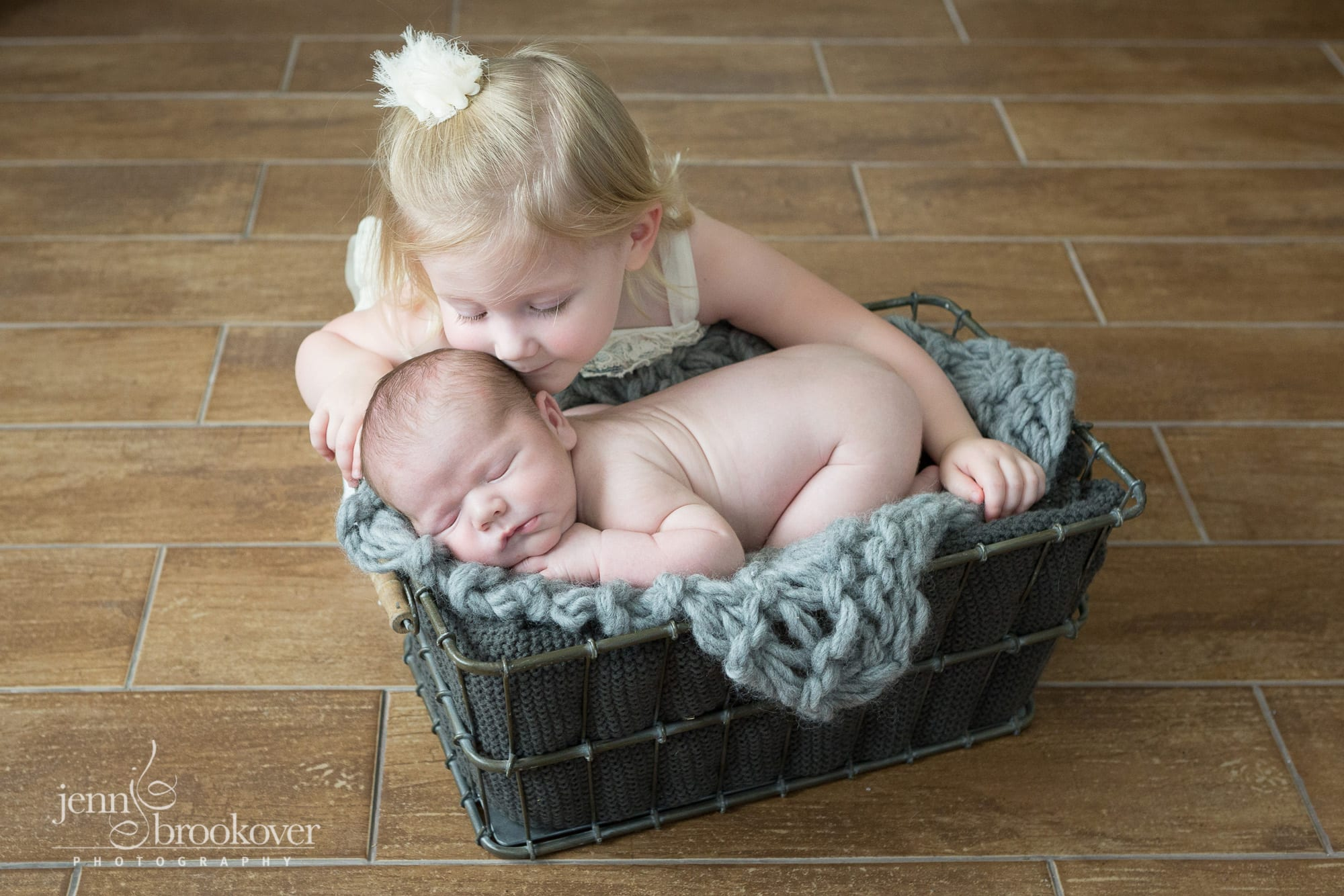 big sister kissing newborn baby brother during photo session