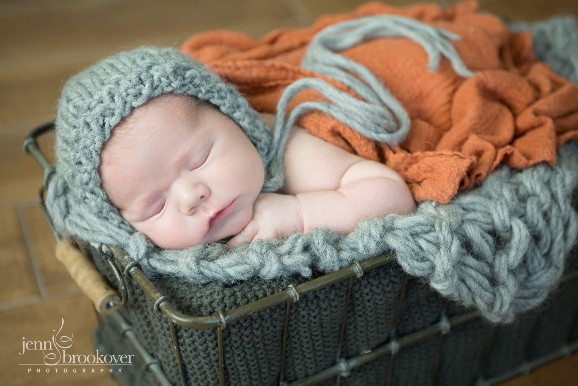 newborn boy in gray bonnet on knitted blanket