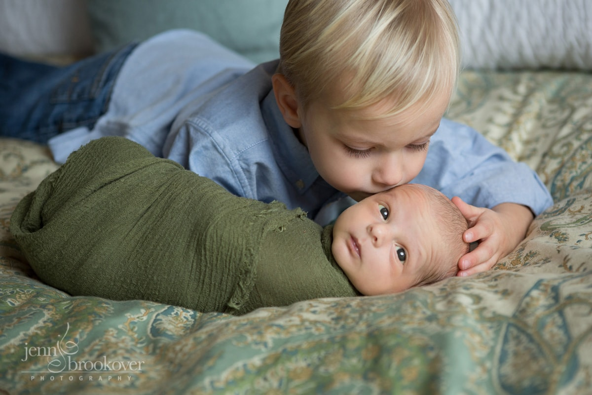 big brother kissing little brother during newborn session at home