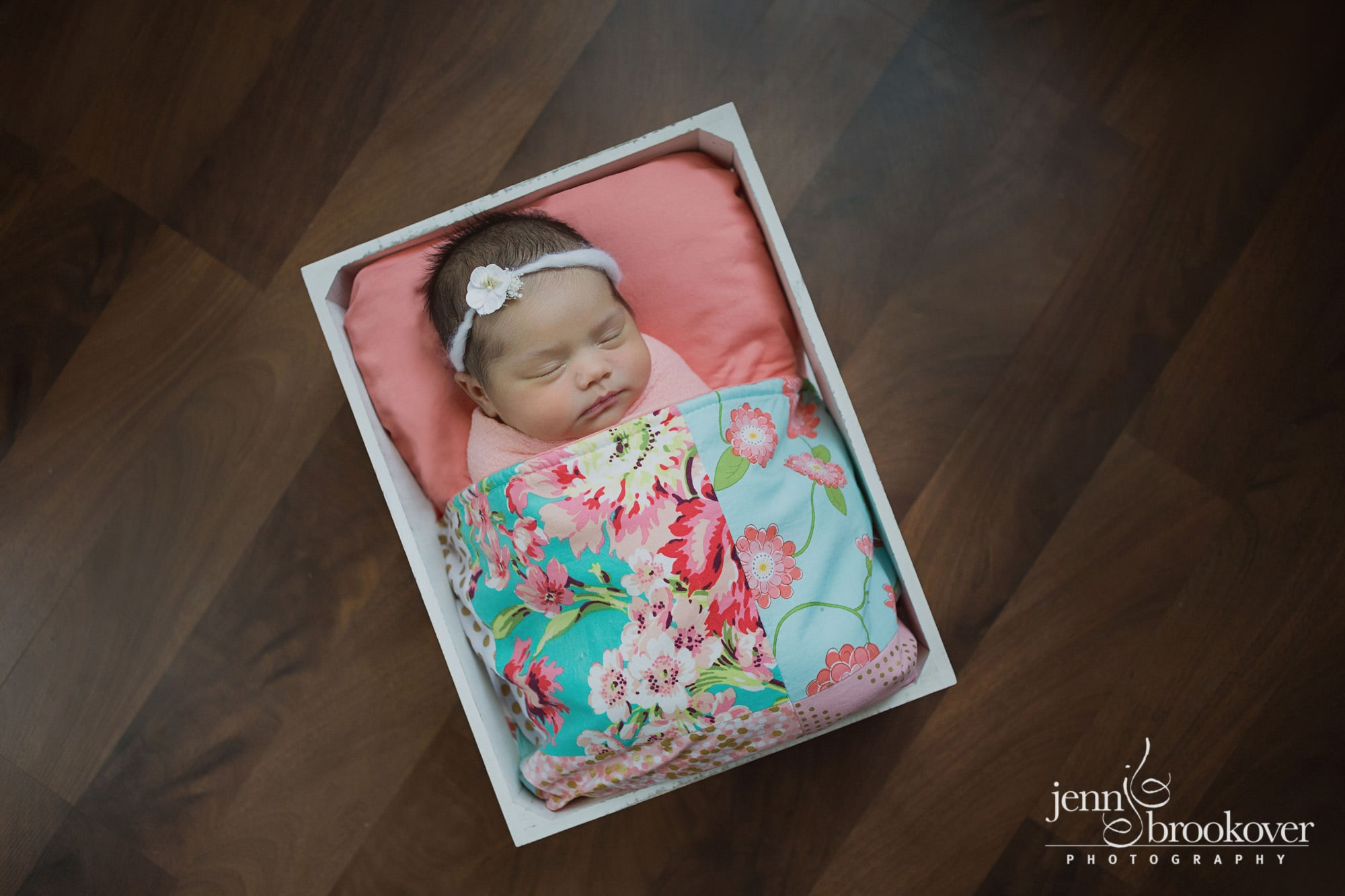 newborn in quilt, peach, coral, mint during her photo session with Jenn Brookover in Texas