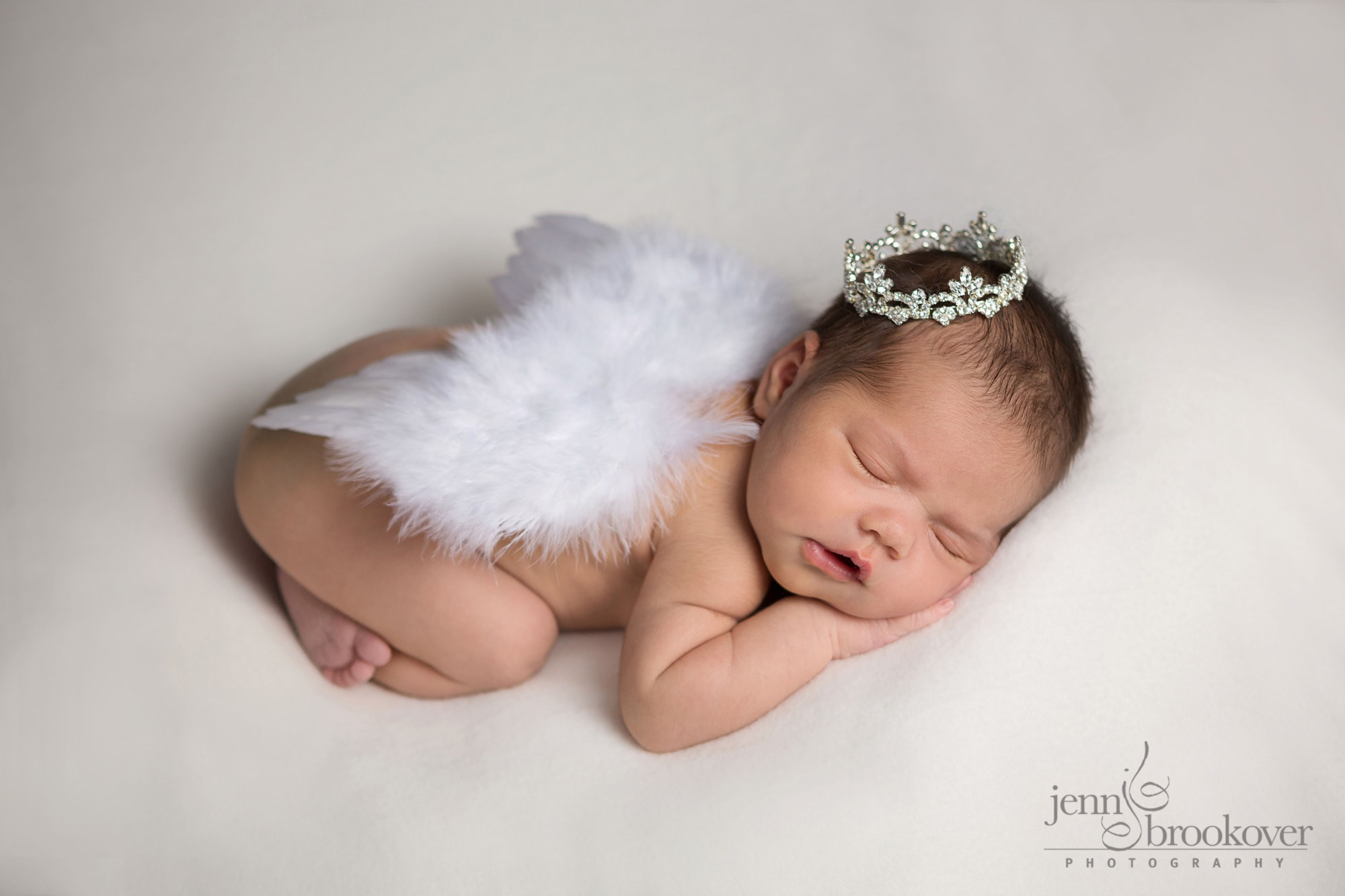 newborn with wings and crown sleeping on white background during her photo shoot with Jenn Brookover Photography in San Antonio