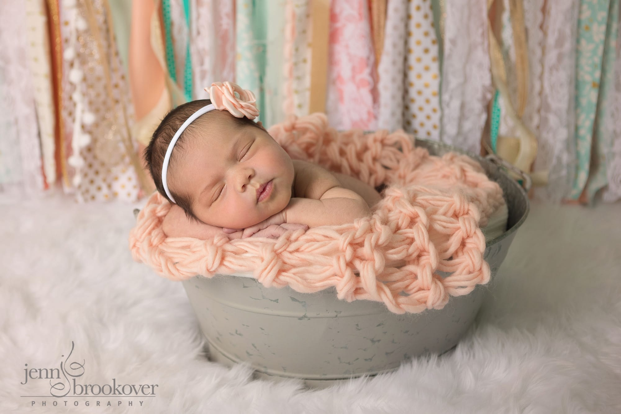 newborn in tin with fabric banner as backdrop taken at home in her nursery in San Antonio by Jenn Brookover