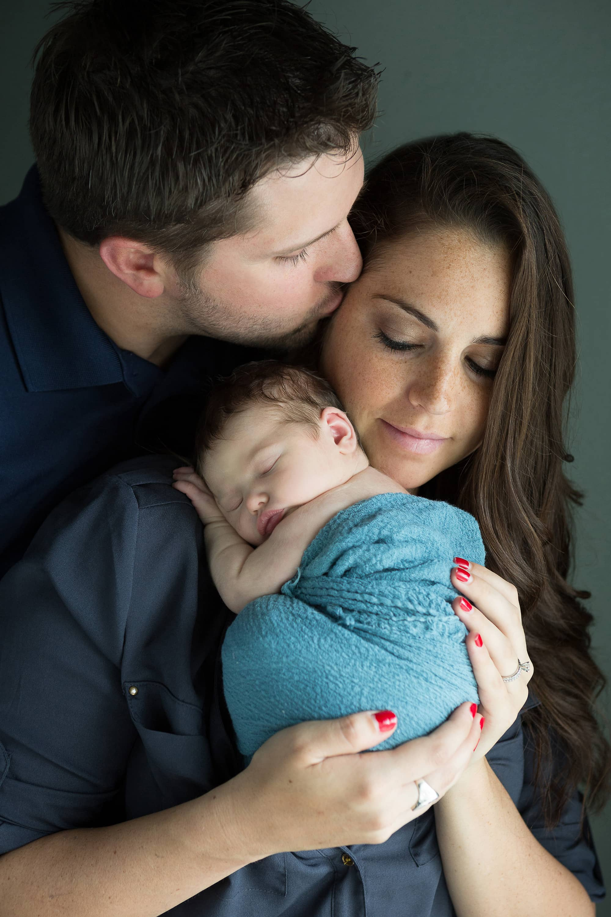 dad kissing mom holding newborn baby girl at home during photo session