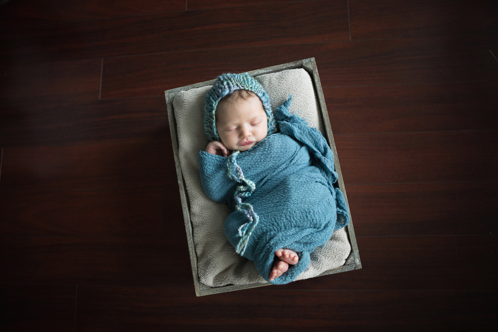newborn in teal hat and wrap during photo session at home in a crate