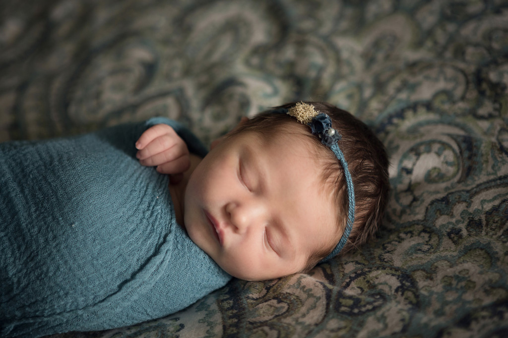 close up of newborn wrapped in teal wearing a Devoted Knits headband