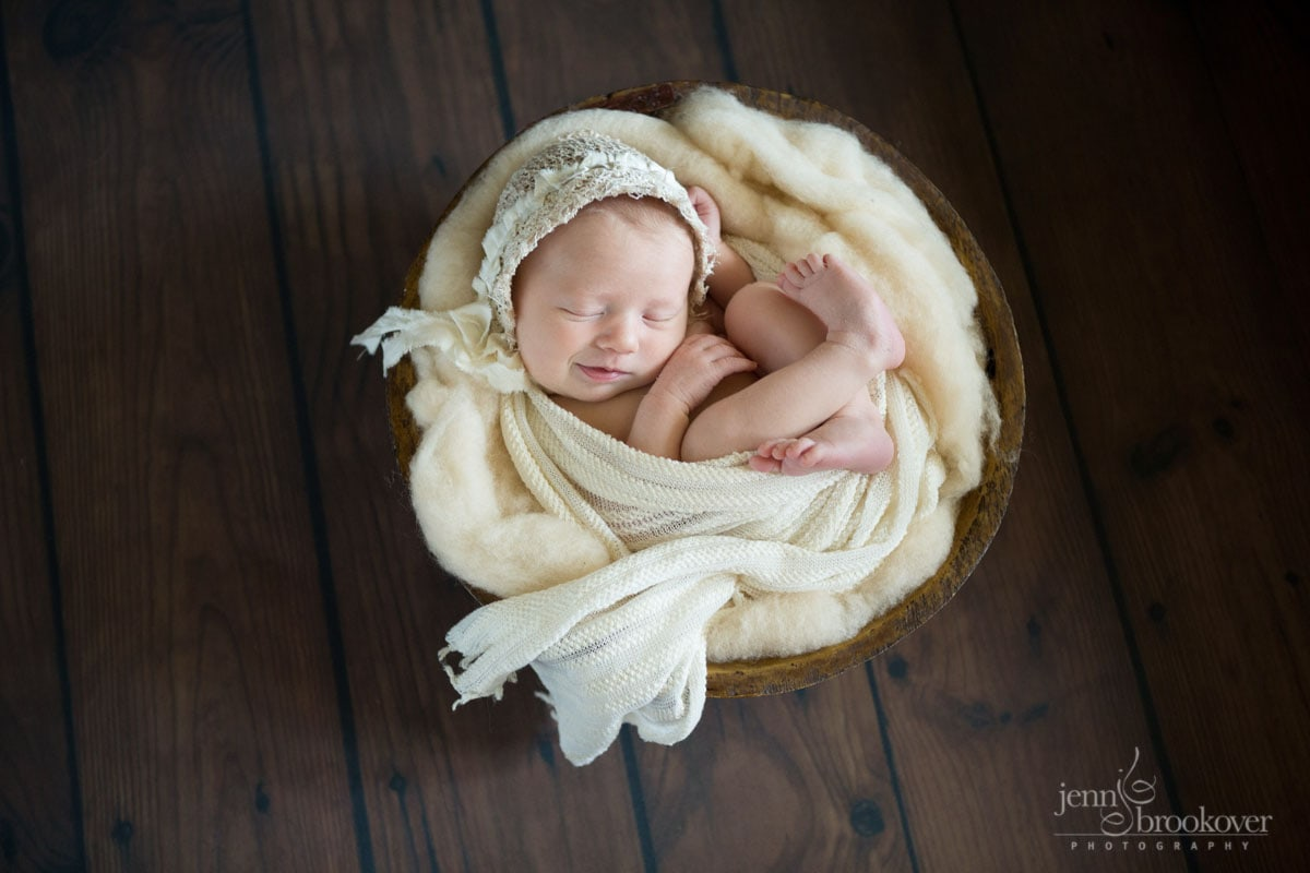 smiling baby wrapped in cream wool and fabric wearing a lace bonnet during photo session with Jenn Brookover