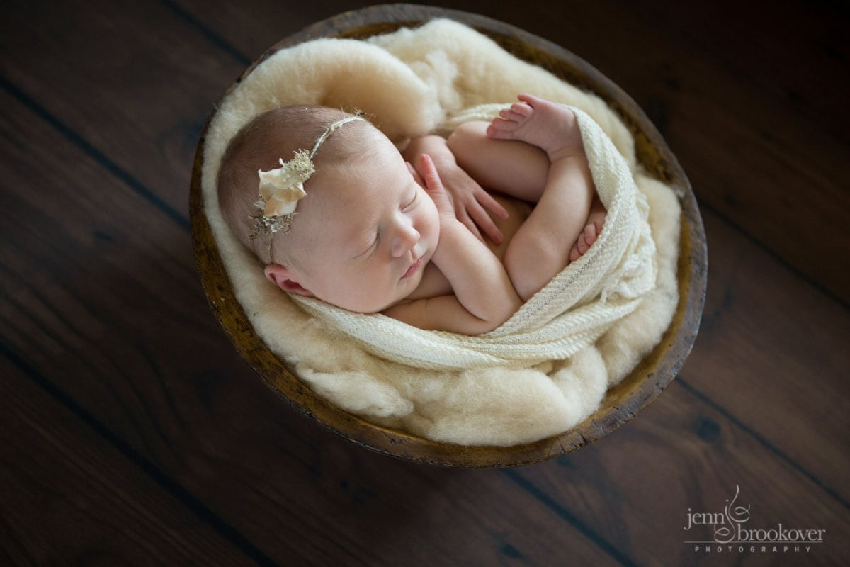 newborn cuddled up in cream wrap with headband by Myrtle and Moss by Jenn Brookover Photography