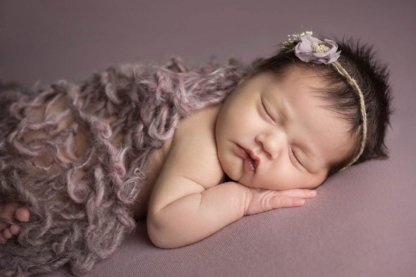 newborn girl in purple with handmade blanket and flower crown